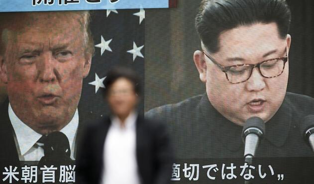 Un peatón camina frente a una pantalla en Tokio, mostrando un informe de prensa relacionado con la decisión del presidente estadounidense Donald Trump de cancelar su reunión con el líder norcoreano Kim Jong Un / AFP