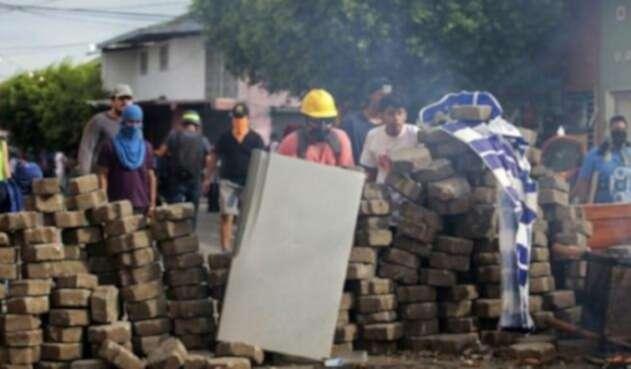 Manifestantes en contra del gobierno del presidente Daniel Ortega se protegen de la represión de la Policía en Masaya