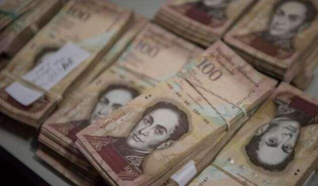 Billetes de 100 bolívares se exhiben en un mostrador de un negocio de repuestos en Los Teques, el 13 de diciembre de 2016