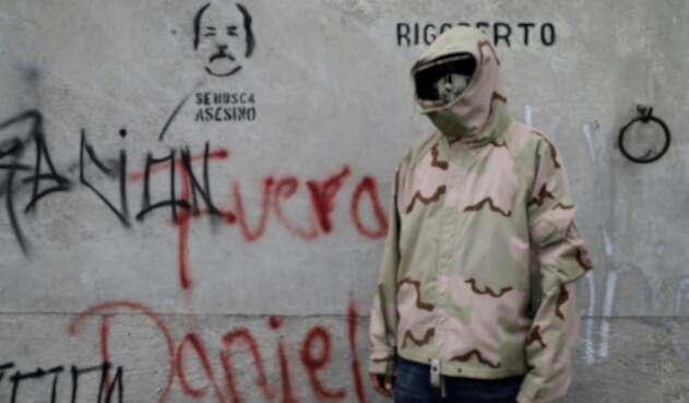 """Un estudiante posa al lado de un grafiti en el que se lee """"Fuera Daniel"""" en alusión al presidente Ortega."""