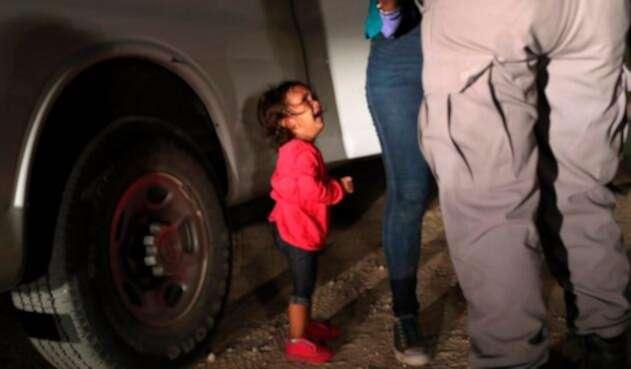 Una niña mirando a un oficial estadounidense tras ser separada de su familia en la frontera