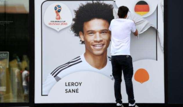 Un empleado de la Federación Alemana de Fútbol retira el afiche de Leroy Sané, en Dortmund