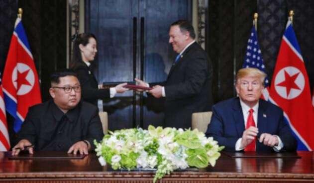 En el fondo Mike Pompeo; en la mesa Kim Jong Un y Donald Trump