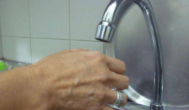 Una persona usando el lavaplatos de su hogar