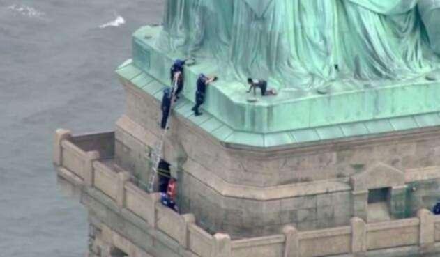 La mujer se encuentra en la base de la Estatua de la Libertad.