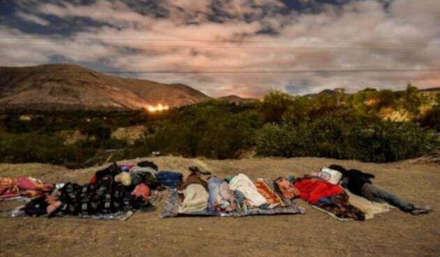 Venezolanos duermen en la vía Panamericana.