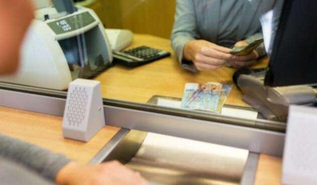 Un ciudadano dejando el dinero en una entidad bancaria