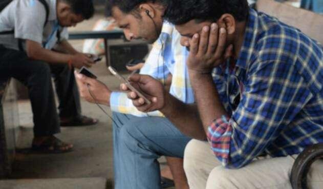 Ciudadanos revisando su celular mientras se movilizan en tren.
