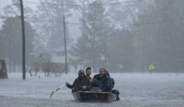 Personas navegando sobre las aguas que dejó Florence