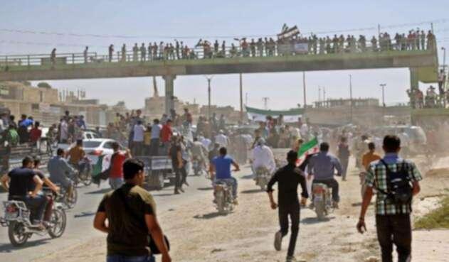 Los sirios entonan consignas y agitan banderas de la oposición mientras protestan contra el régimen y su aliado Rusia