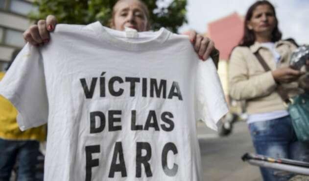 """Una mujer sostiene una camiseta con la leyenda """"Víctima de las Farc"""" durante una protesta afuera en la sede de la Jurisdicción Especial para la Paz (JEP) en Bogotá, el 13 de julio de 2018."""
