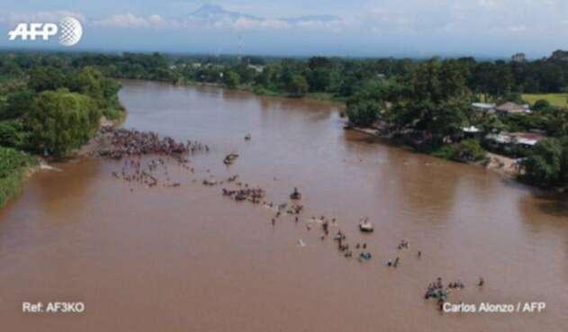 La caravana de migrantes cruza a pie el río que separa Guatemala de México.
