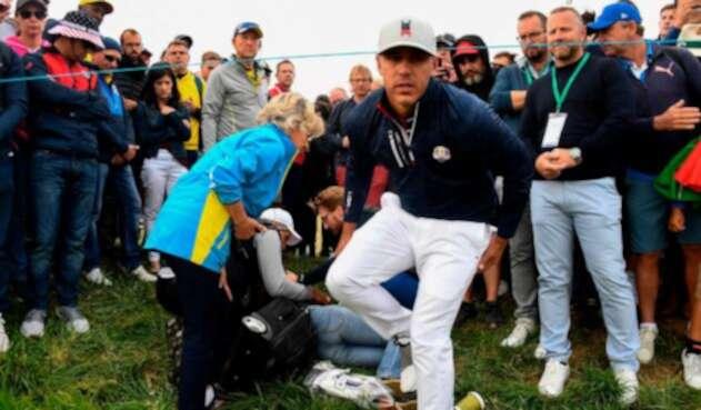 El golfista Brooks Koepka tratar de auxiliar a una espectadora que recibió el golpe de una bola en su ojo derecho