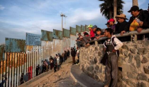 Migrantes centroamericanos en muro de Estados Unidos