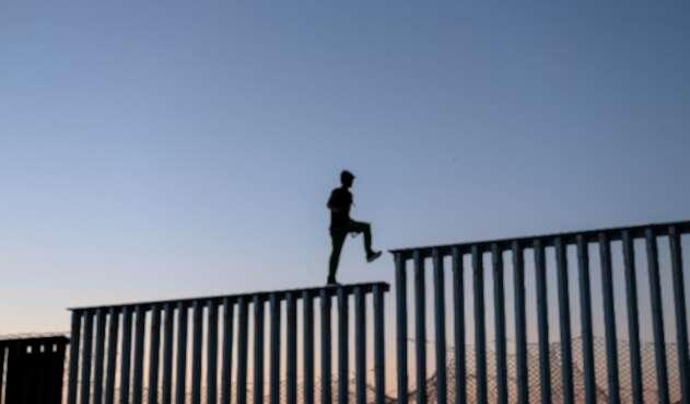 Migrantes en el muro entre México y Estados Unidos