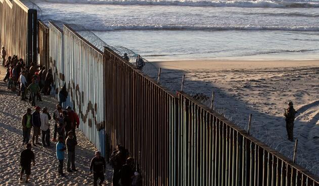 Así se han visto los migrantes centroamericanos en un muro que divide a México con Estados Unidos.