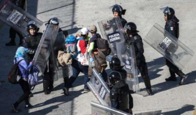 Migrantes intentan cruzar muro con EE.UU. y reciben gas lacrimógeno.