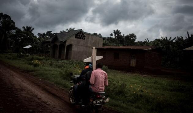 Tres congoleños montan una motocicleta y llevan una cruz por una tumba a lo largo de la carretera que une Mangina con Beni el 23 de agosto de 2018 en Mangina, en la provincia de Kivu Norte. Según informaron las autoridades, sesenta y una personas murieron en el último brote de ébola en la República Democrática del Congo (RDC), y agregaron que se habían agregado cuatro nuevos medicamentos a la lista de tratamientos.