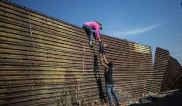 Un grupo de migrantes centroamericanos trepó la valla fronteriza entre México y Estados Unidos, cerca del cruce fronterizo de El Chaparral, en Tijuana, estado de Baja California, México, el 25 de noviembre de 2018. Cientos de migrantes intentaron asaltar una valla fronteriza que separa a México de El domingo, EE.UU., en medio de crecientes temores, permanecerán en México mientras se procesan sus solicitudes de asilo.