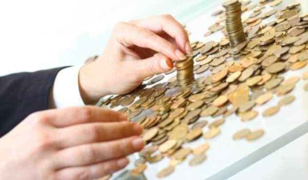 Una persona contando sus ahorros en moneda