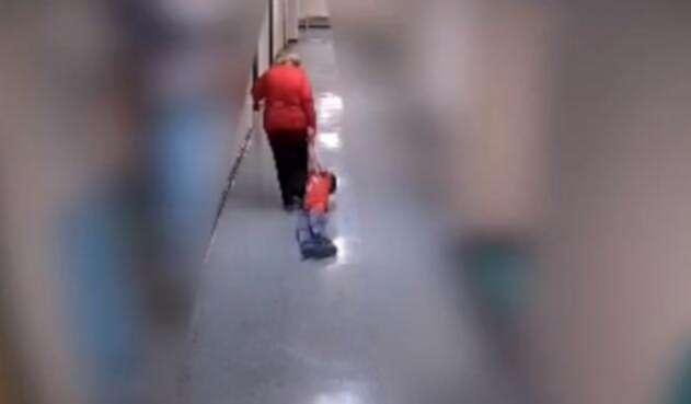 Profesora arrastra a un niño en una escuela
