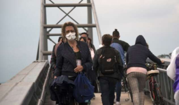 Mujer cruza puente peatonal con tapabocas