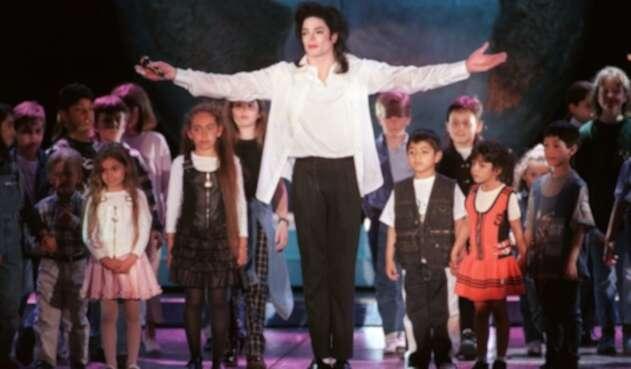 Michael Jackson canta junto a niños en un escenario en Mónaco, Francia (1996).