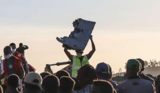 Una persona sujeta una parte del avión siniestrado en Bishoftu, en inmediaciones de Addis Ababa, en Etiopía