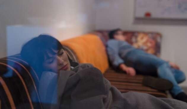 Una pareja tratando de dormir en un sofá