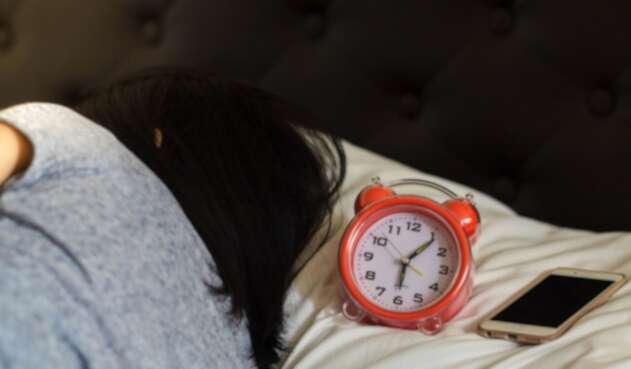 Una mujer trata de dormir, pero no deja lejos su teléfono celular