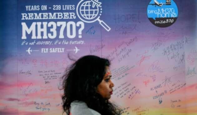 Una mujer camina en Kuala Lumpur (Malasia) mientras de fondo se observa un afiche que da cuenta de la desaparición del vuelo de Malaysia Airlines en 2014