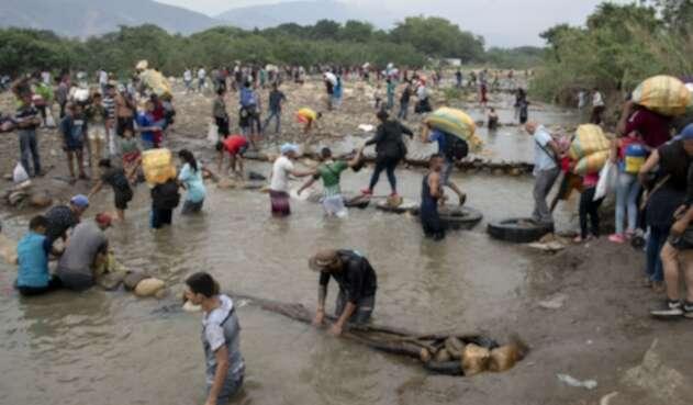 Venezolanos cruzando la frontera por el río
