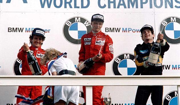 Niki Lauda acompañado en el podio por Alain Prost y Ayrton Sena