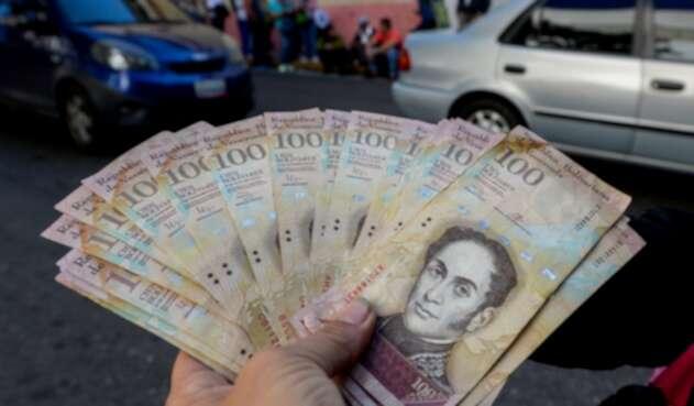 Un ciudadano venezolano expone bolívares, moneda oficial, en las calles de Caracas