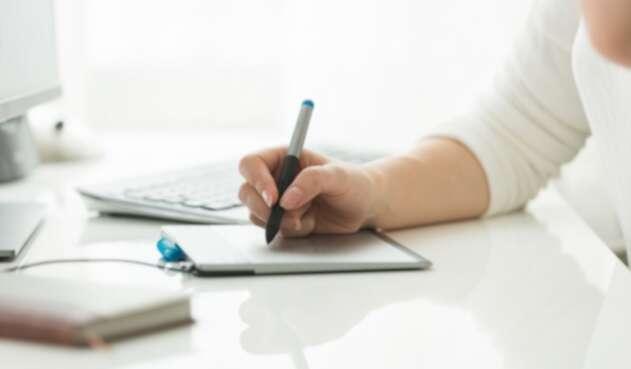 Una persona usando su tablet para estudiar