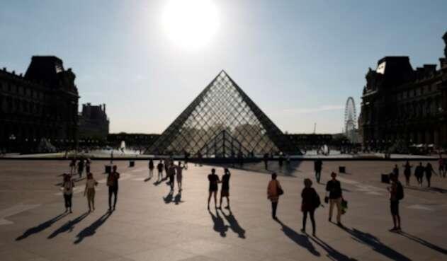 Turistas visitando la Pirámide del Museo del Louvre, en París (Francia), el 3 de julio de 2019