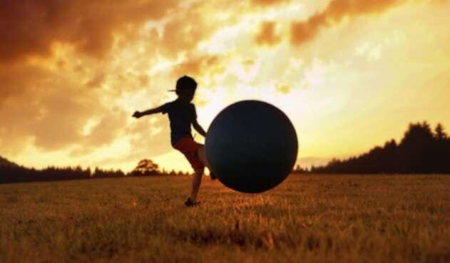 Niño jugando fútbol.