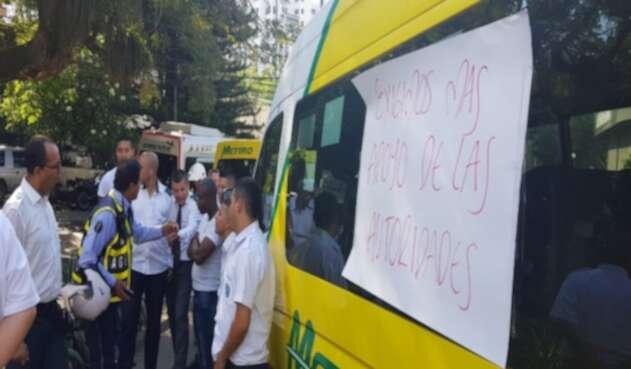 Decenas de vehículos de transporte bloquean la vía, reclamando que el transporte ilegal les está quitando sus recursos.