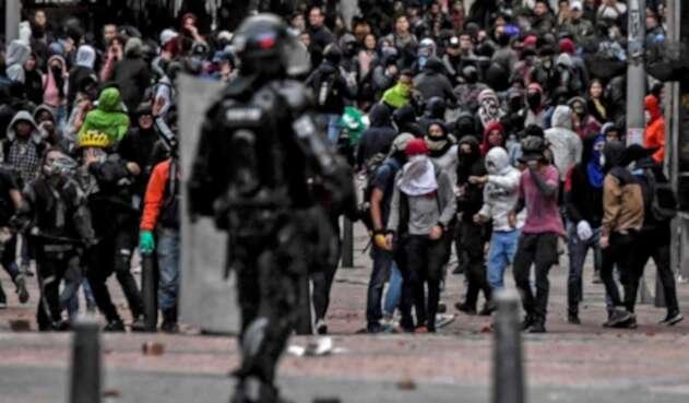 Agente del Esmad enfrenta disturbios y desórdenes en la capital colombiana.