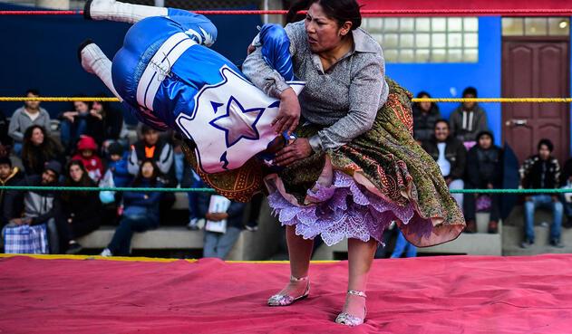Con falda ondulante de brillantes, las luchadoras se lanzan al combate.