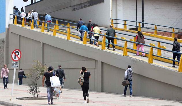 Personas entrando y saliendo de un centro comercial.
