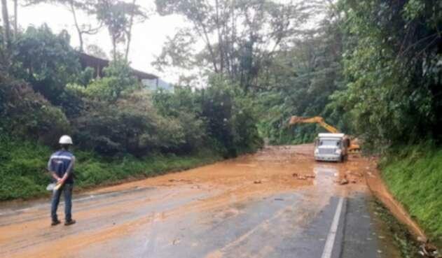 Con maquinaria amarilla tratan de remover los escombros que obstruyen la vía.