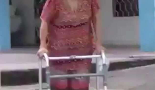 La mujer utiliza un tubo de PVC para poder caminar.